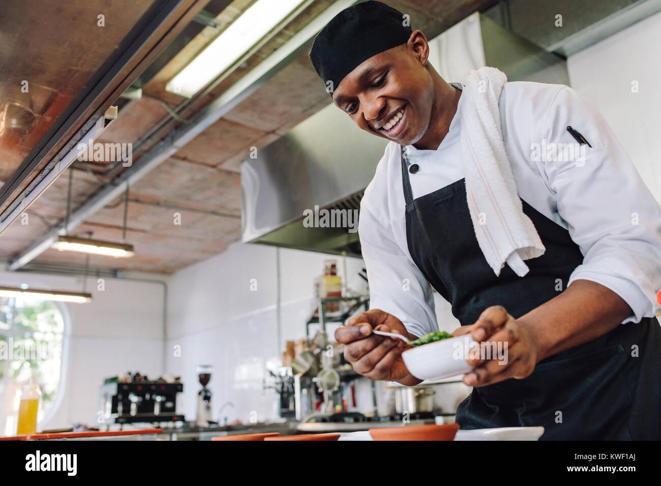 Gourmet chef en uniforme dans la cuisine une cuisine commerciale. Heureux homme cook Portant tablier, debout par Photo Stock