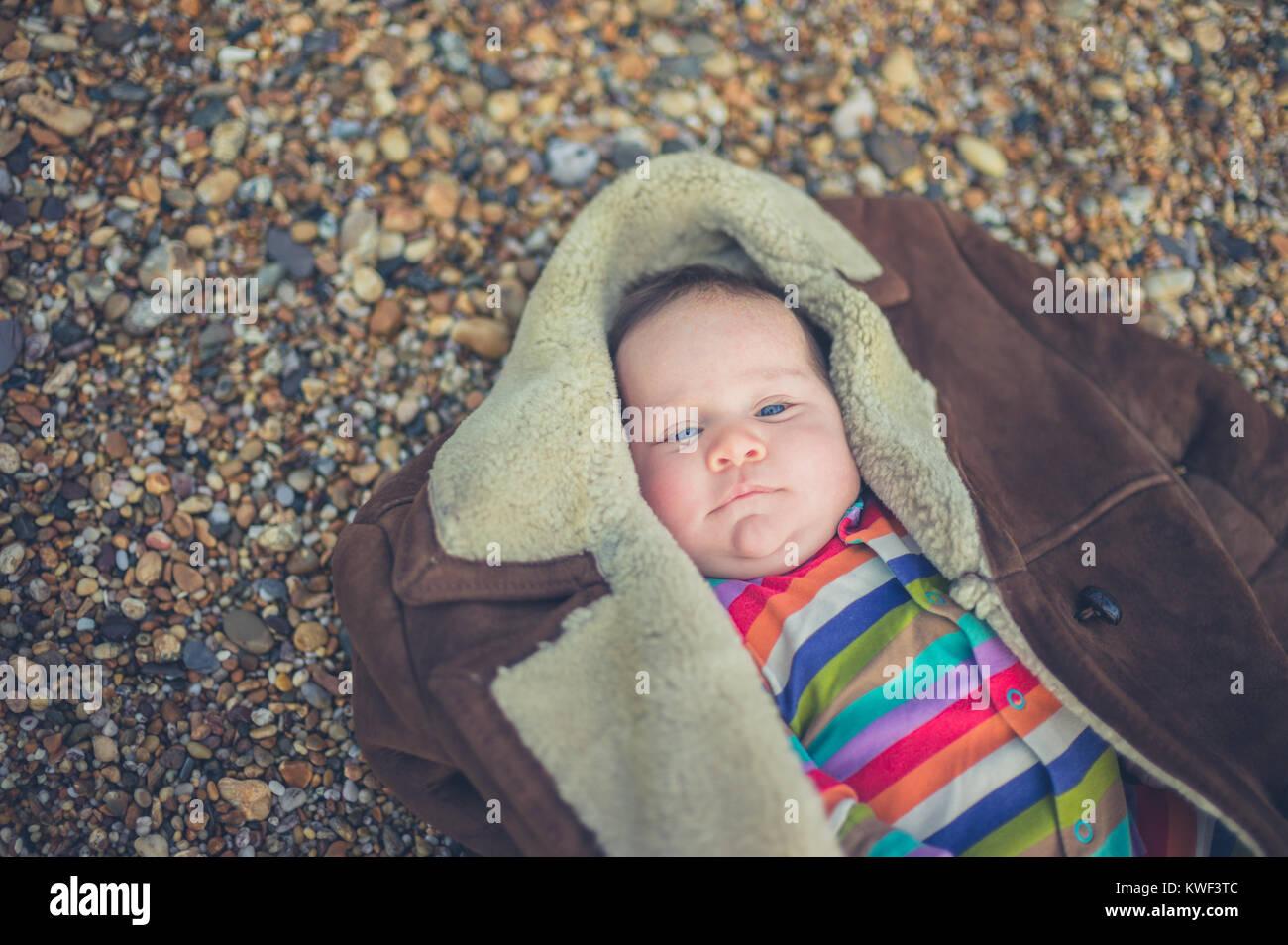 Un petit bébé est enveloppé dans un manteau sur la plage Photo Stock
