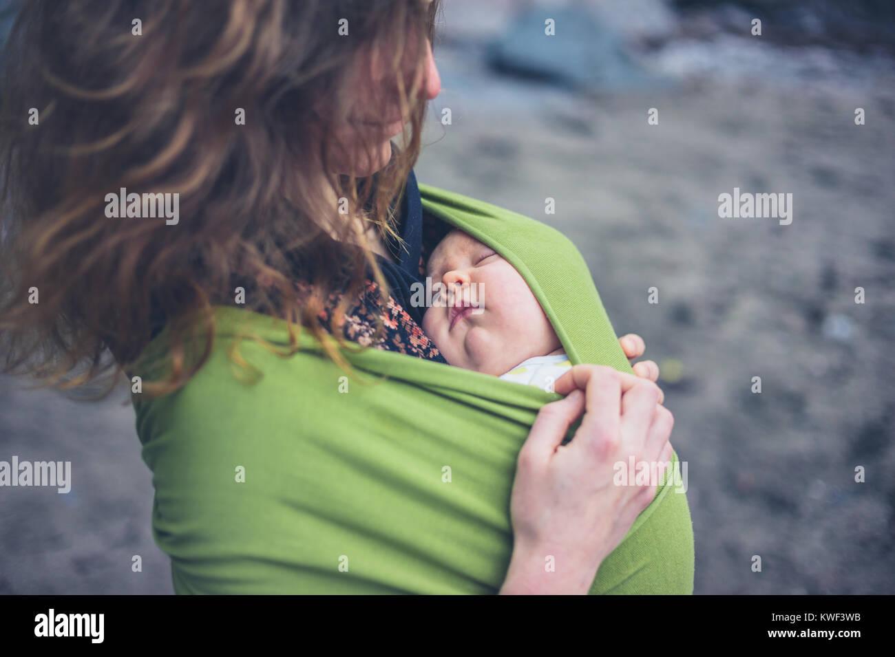 Une jeune femme sur la plage avec son bébé dans une écharpe Photo Stock