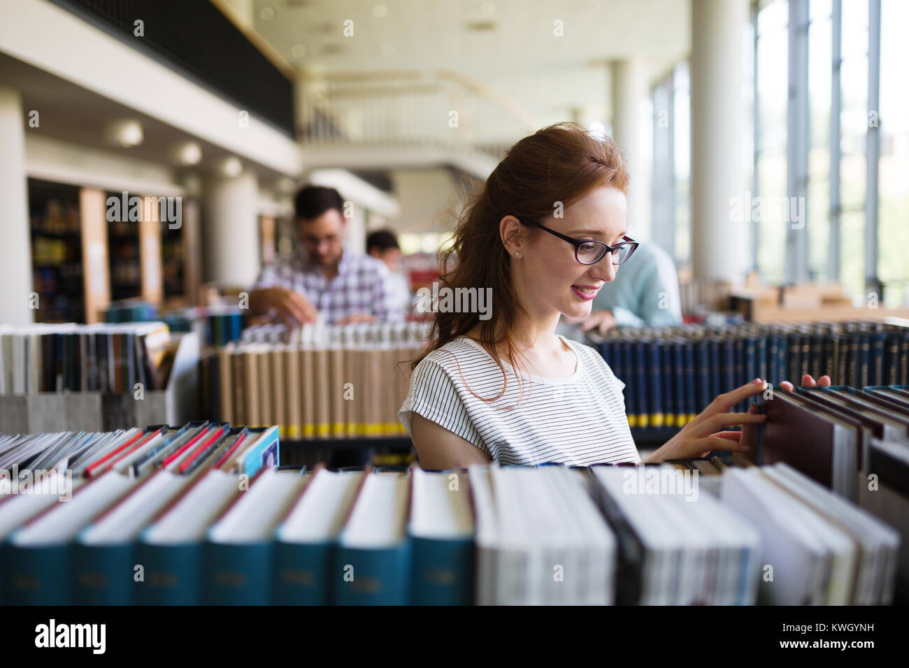 Portrait of a pretty smiling girl reading book in library Photo Stock