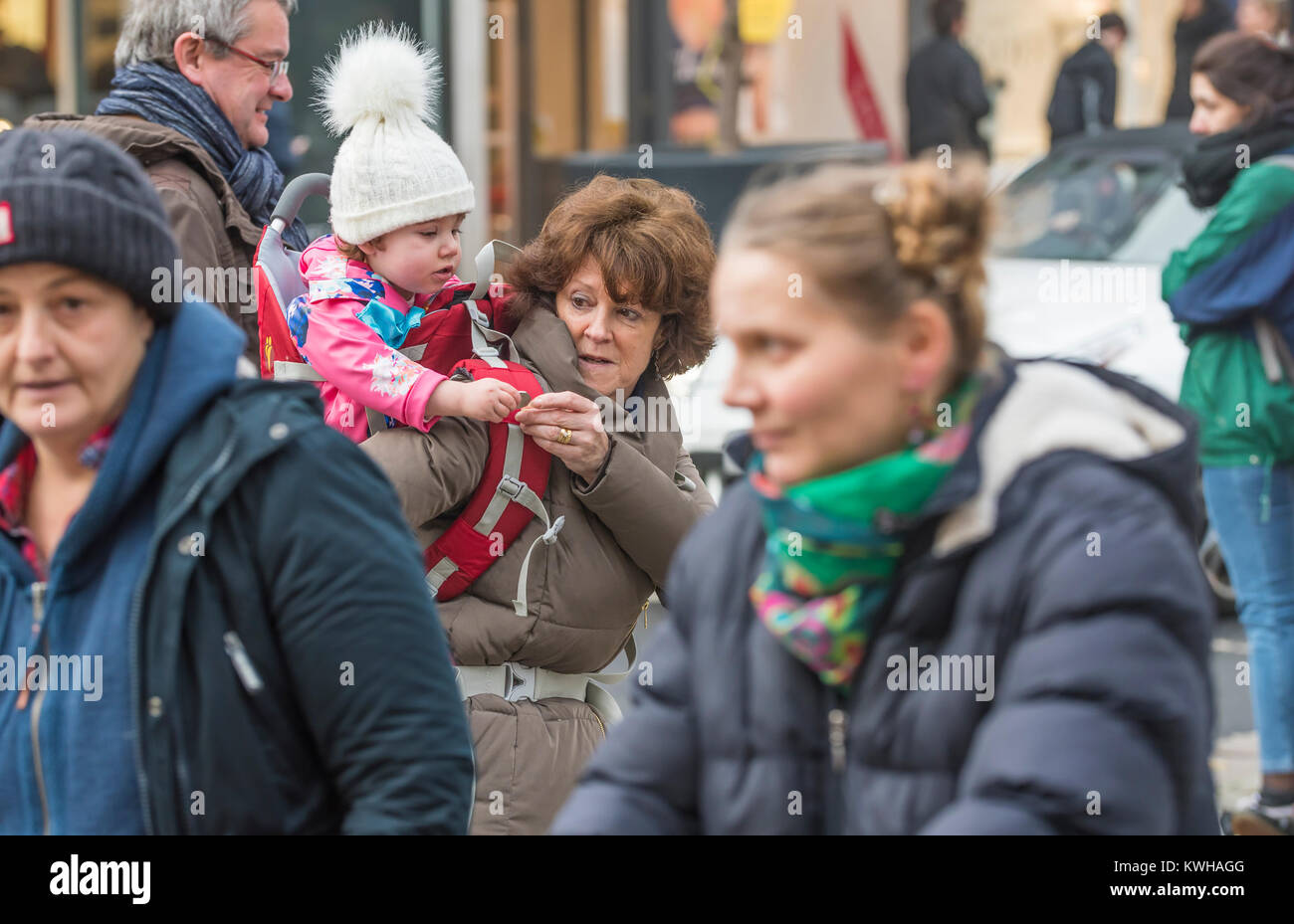 Femme portant un enfant sur ses épaules, un piggy back ride, parmi la foule dans une rue animée de l'Angleterre, Banque D'Images