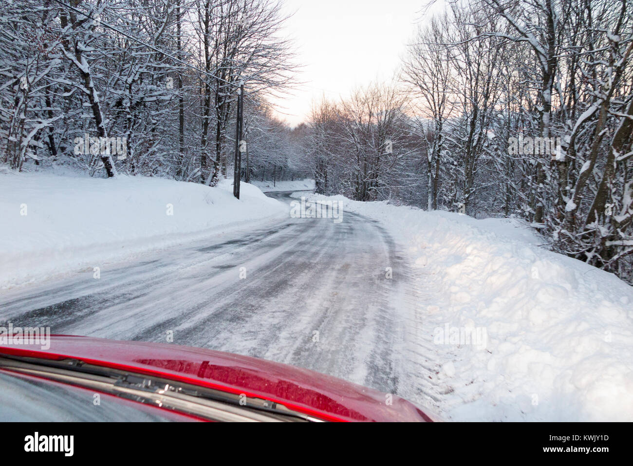 Neige glissante recouverte de glace alpine française country road, avec de la glace, après un blizzard, vu à travers le pare-brise de l'intérieur de la voiture à la tombée de la nuit. Alpes Banque D'Images