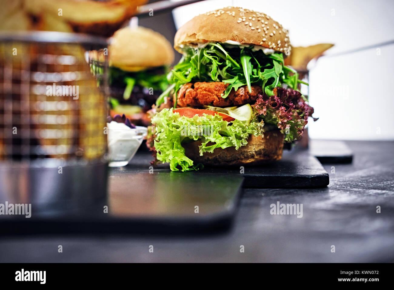 Burger, frites avec salade sur une table. Photo Stock