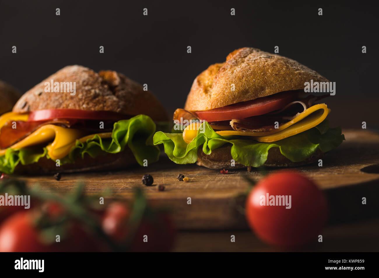 Des sandwichs avec du fromage sur planche de bois sur table avec tomates cerise sur le premier plan Photo Stock