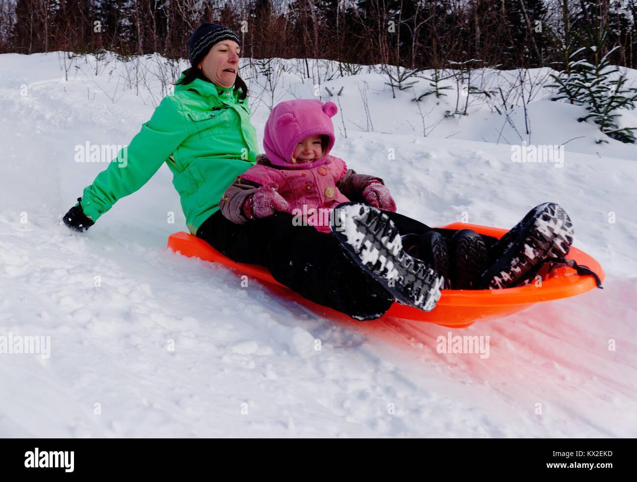 Une femme adulte dans un traîneau avec une petite fille (3 ans) à la recherche comme son nerveux beaucoup Photo Stock