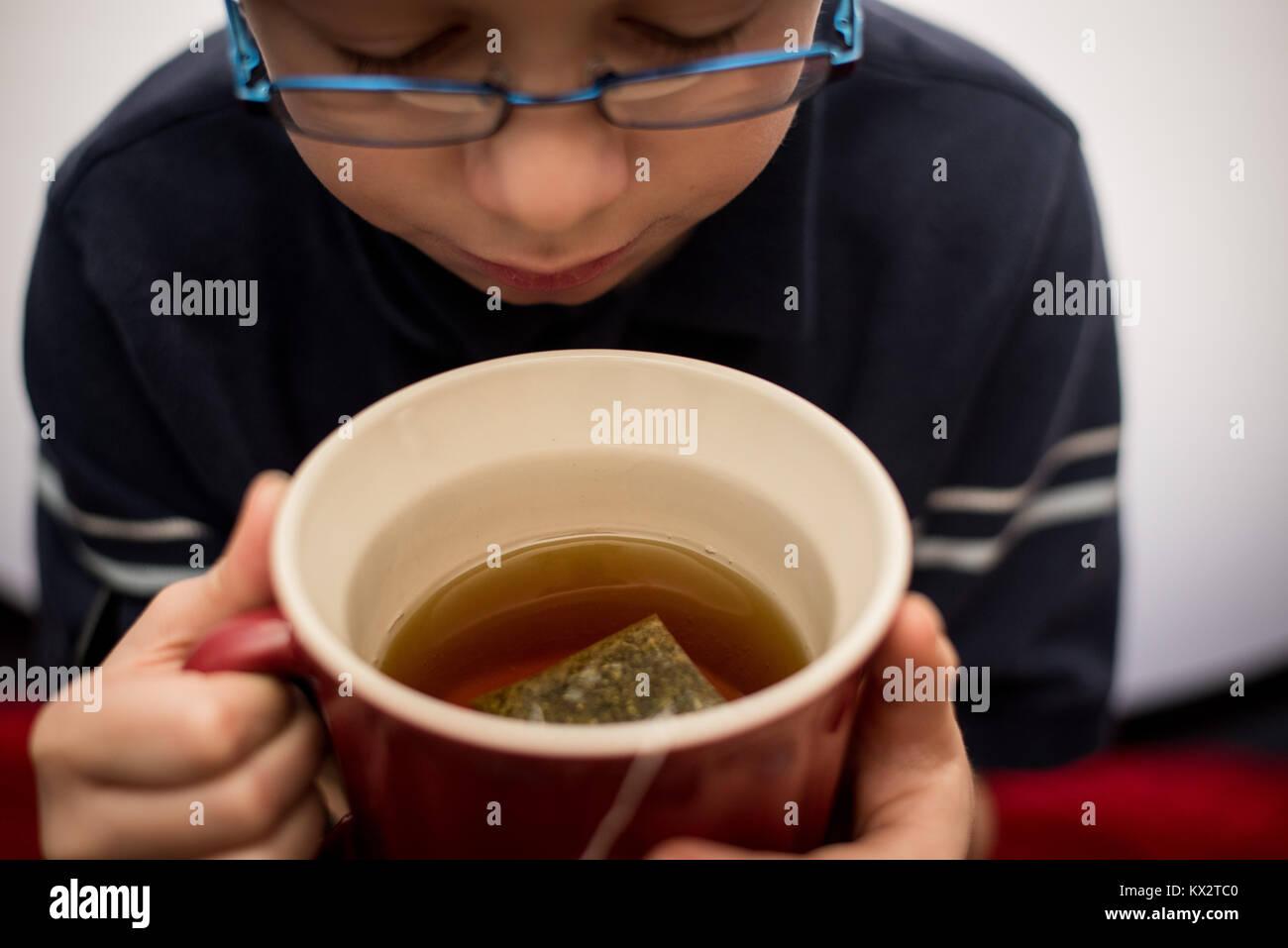 Un jeune garçon boit dans une tasse de thé dans une tasse rouge. Photo Stock