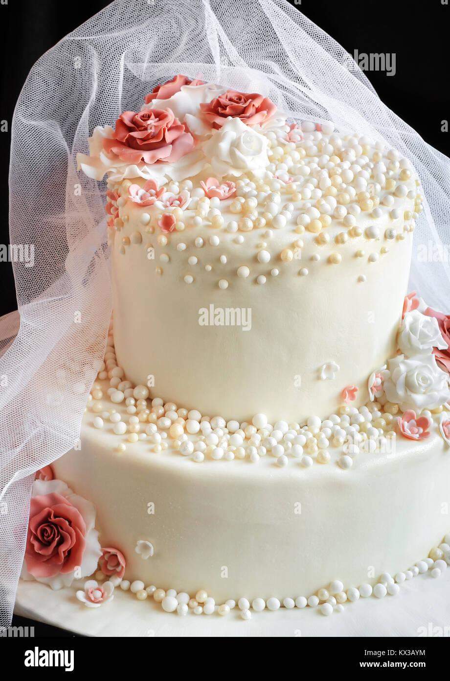 Voile sur le gâteau de mariage avec des roses sur fond noir Photo Stock