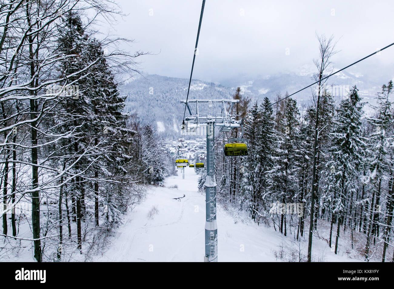 Télésiège de ski réunissant les skieurs et les surfeurs de la montagne Skrzyczne après les fortes chutes de neige sur une journée d'hiver brumeux de ski à Szczyrk en Pologne Banque D'Images