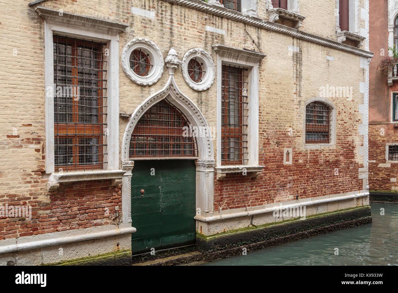 Porte et fenêtres à volets construction le long d'un petit canal en Vénétie, Venise, Italie, Photo Stock