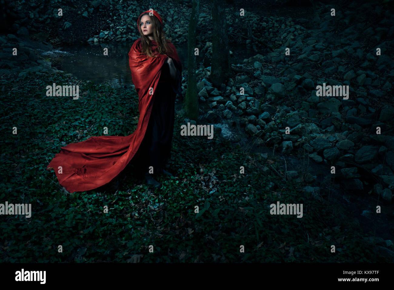 Jeune femme enveloppée dans cape rouge et le capot Banque D'Images