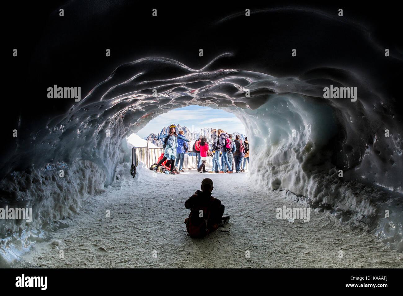 Les touristes qui pose pour photo en face de l'entrée de style grotte de glace, Chamonix Mont Blanc, Haute Savoie, France Banque D'Images