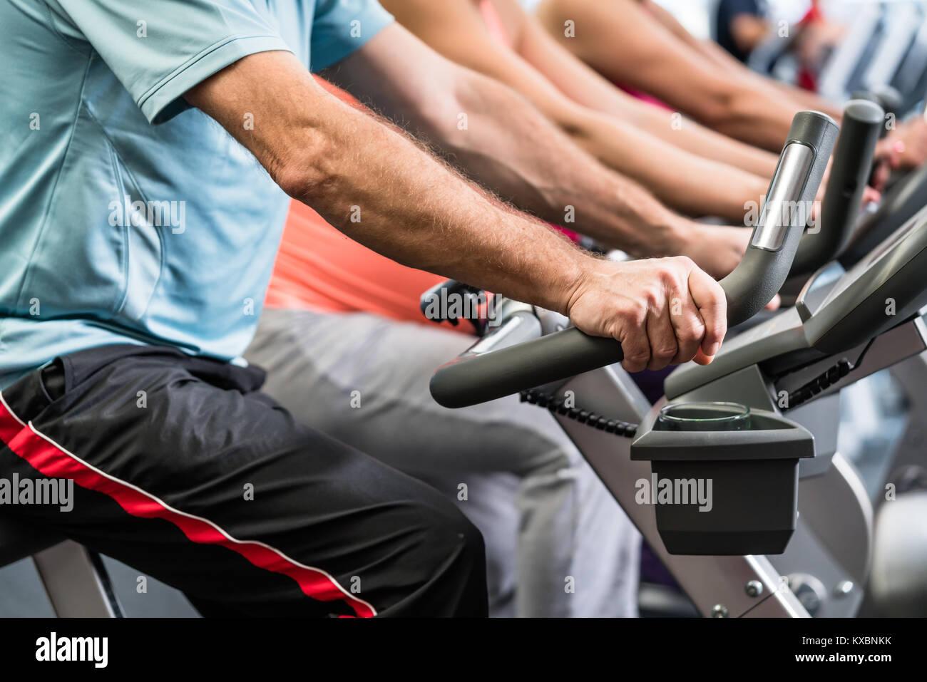 La filature du groupe à la salle de sport sur des vélos de remise en forme Photo Stock