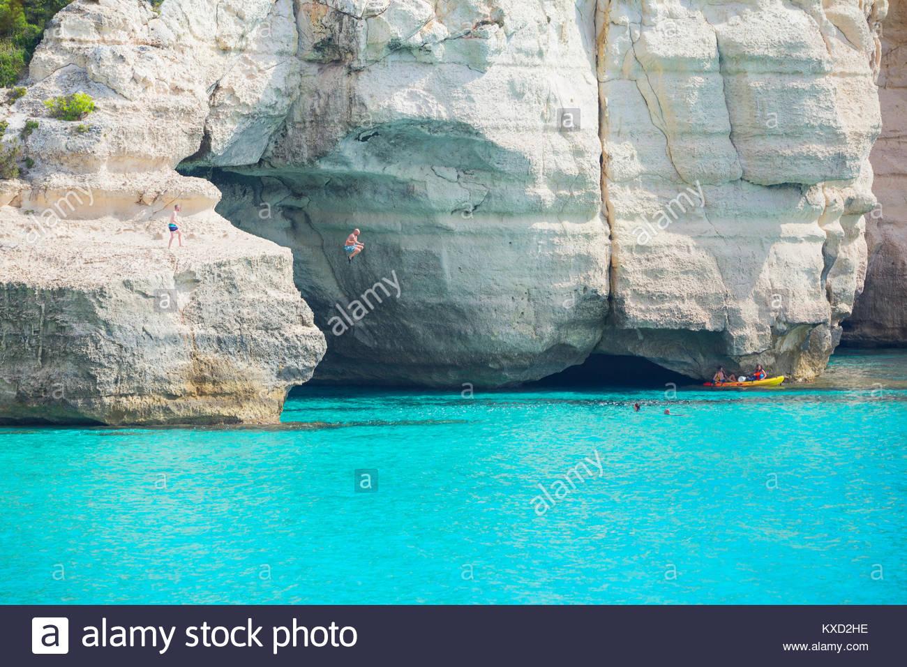 Personnes canoë et sauter dans l'eau, près de Cala Mitjana, Minorque, Iles Baléares, Espagne Photo Stock