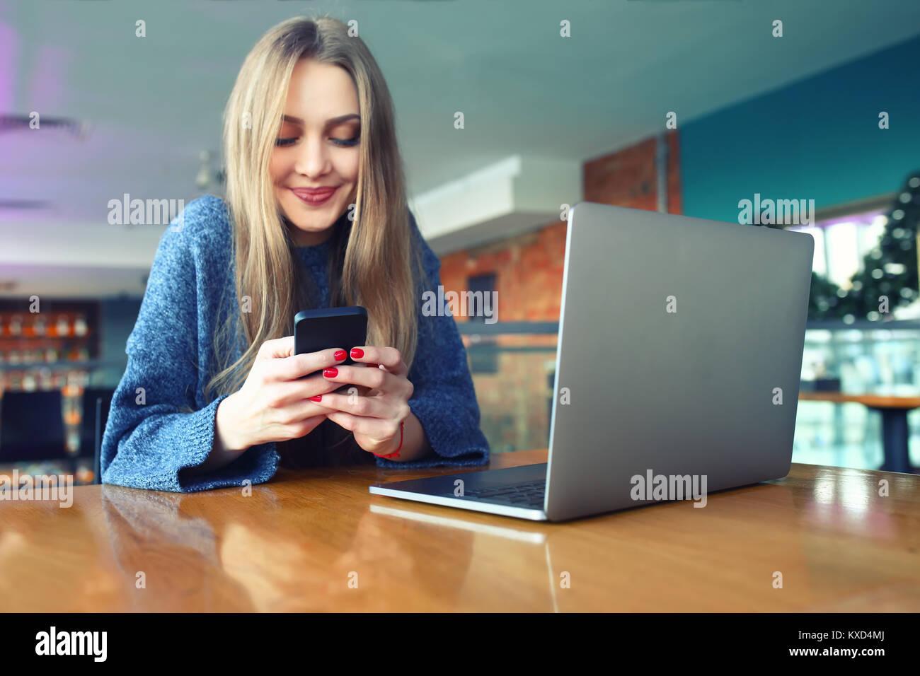 Femme saisissez du texte message sur smart phone dans un café. Jeune femme assise à une table avec un Photo Stock