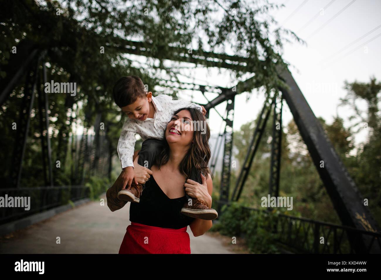 Cheerful mère portant son on shoulders à bridge Photo Stock