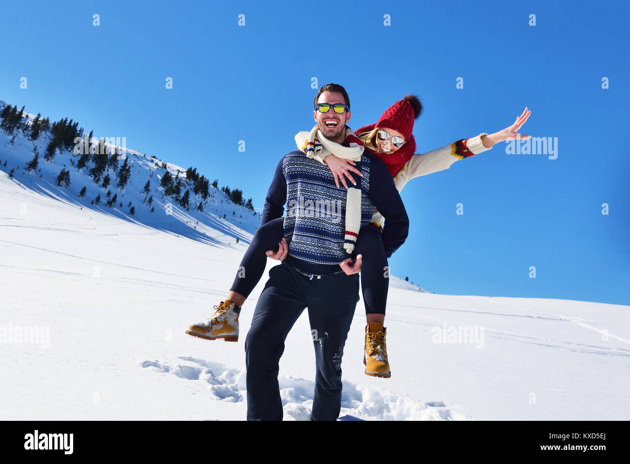 Young couple having fun sur la neige. Heureux l'homme à la montagne donnant à son piggyback ride smiling Photo Stock