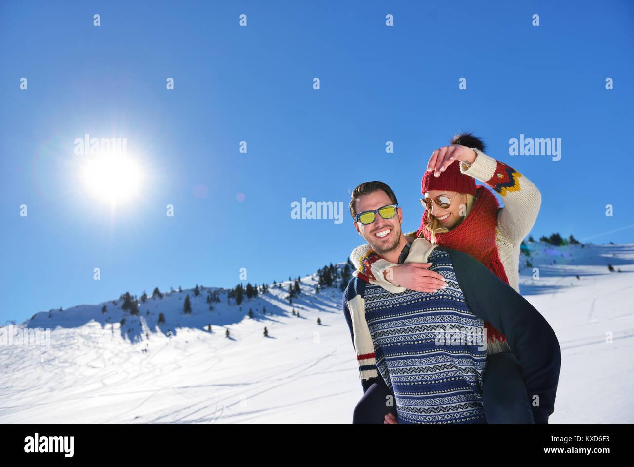 Young couple having fun sur la neige. Heureux l'homme à la montagne donnant à son piggyback ride smiling Photo Stock