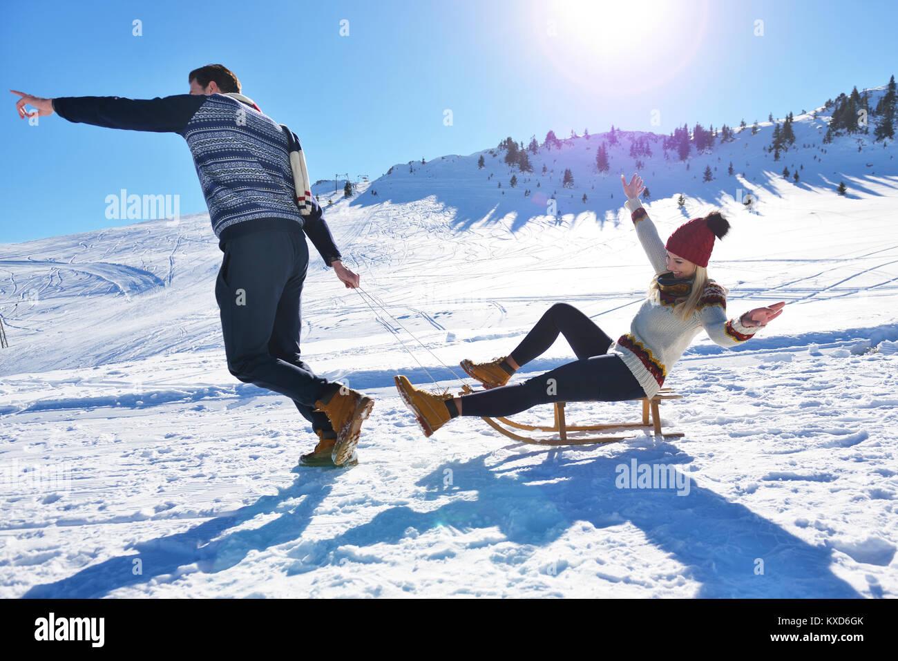 Jeune couple de traîneaux et de profiter aux beaux jours d'hiver Photo Stock