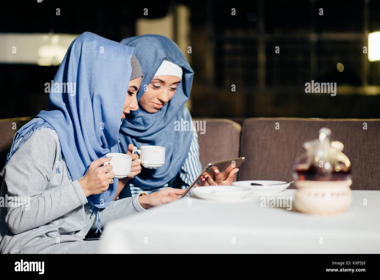 Jolie femme musulmane utiliser tablet in cafe Photo Stock