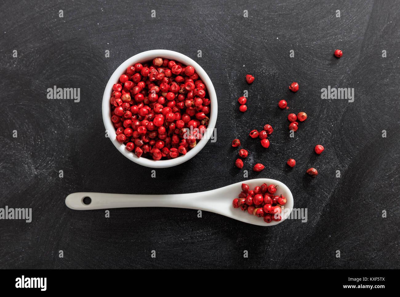 Poivre rouge graines d'épices dans une cuillère et Bol en porcelaine, fond noir Photo Stock
