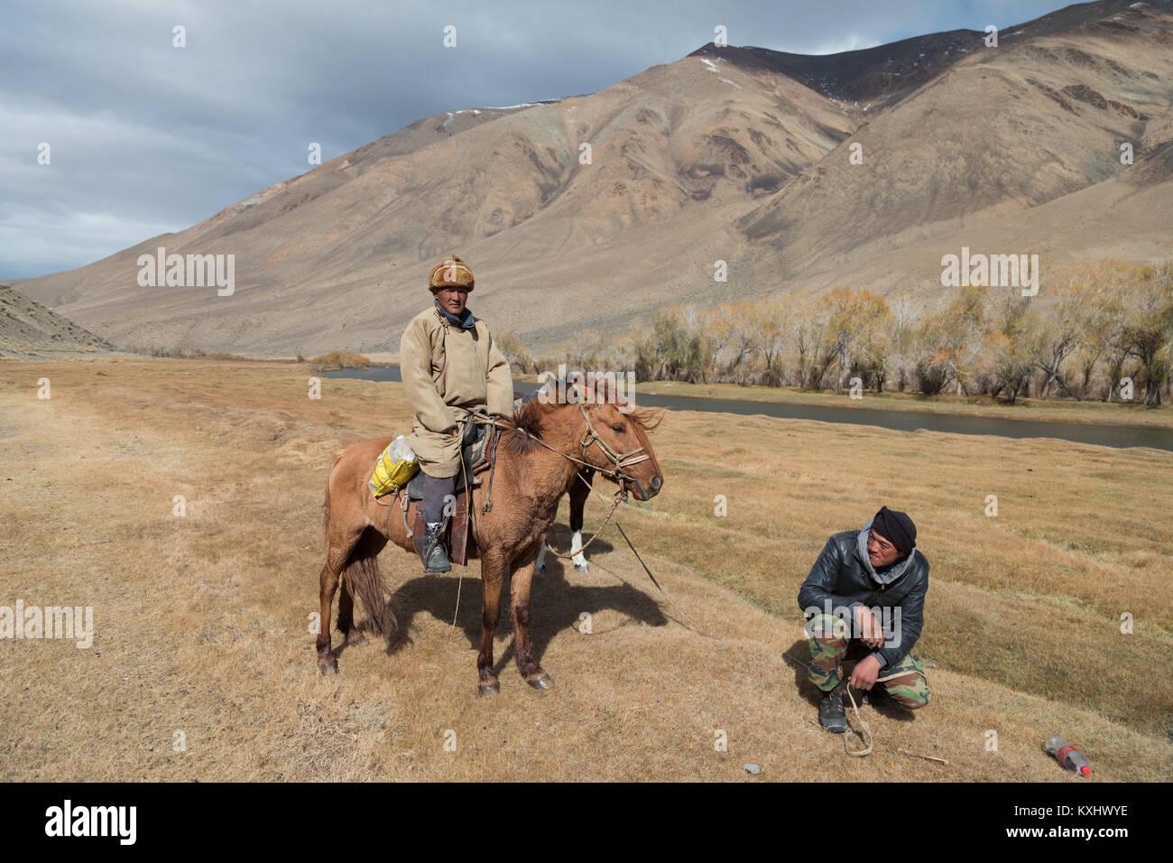 Les cavaliers mongols se reposant à côté de montagnes de la rivière d'hiver en Mongolie Photo Stock