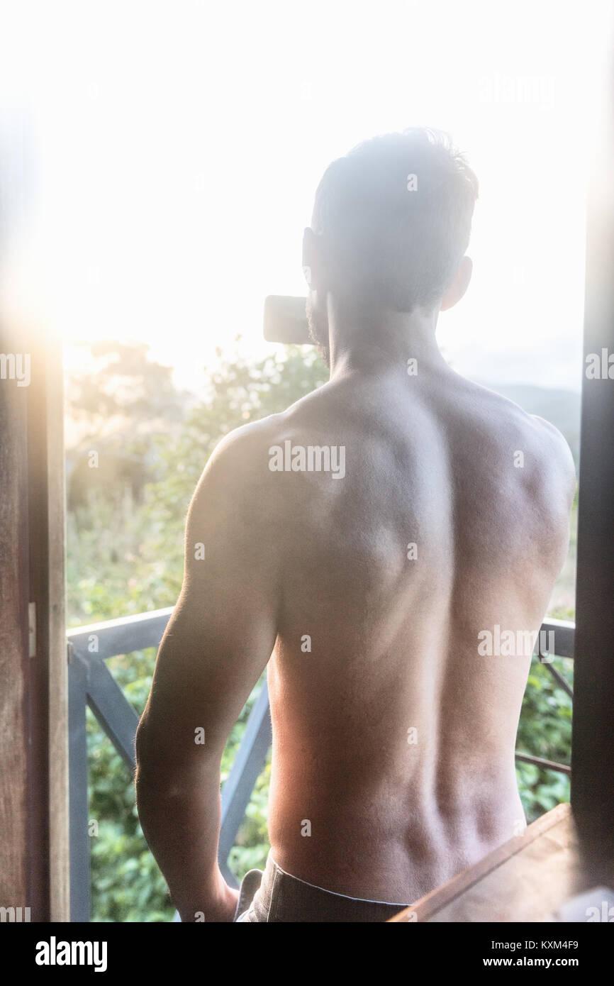 Vue arrière du torse nu man photographing sunlit vue du balcon,Guaramiranga, Ceara, Brésil Photo Stock