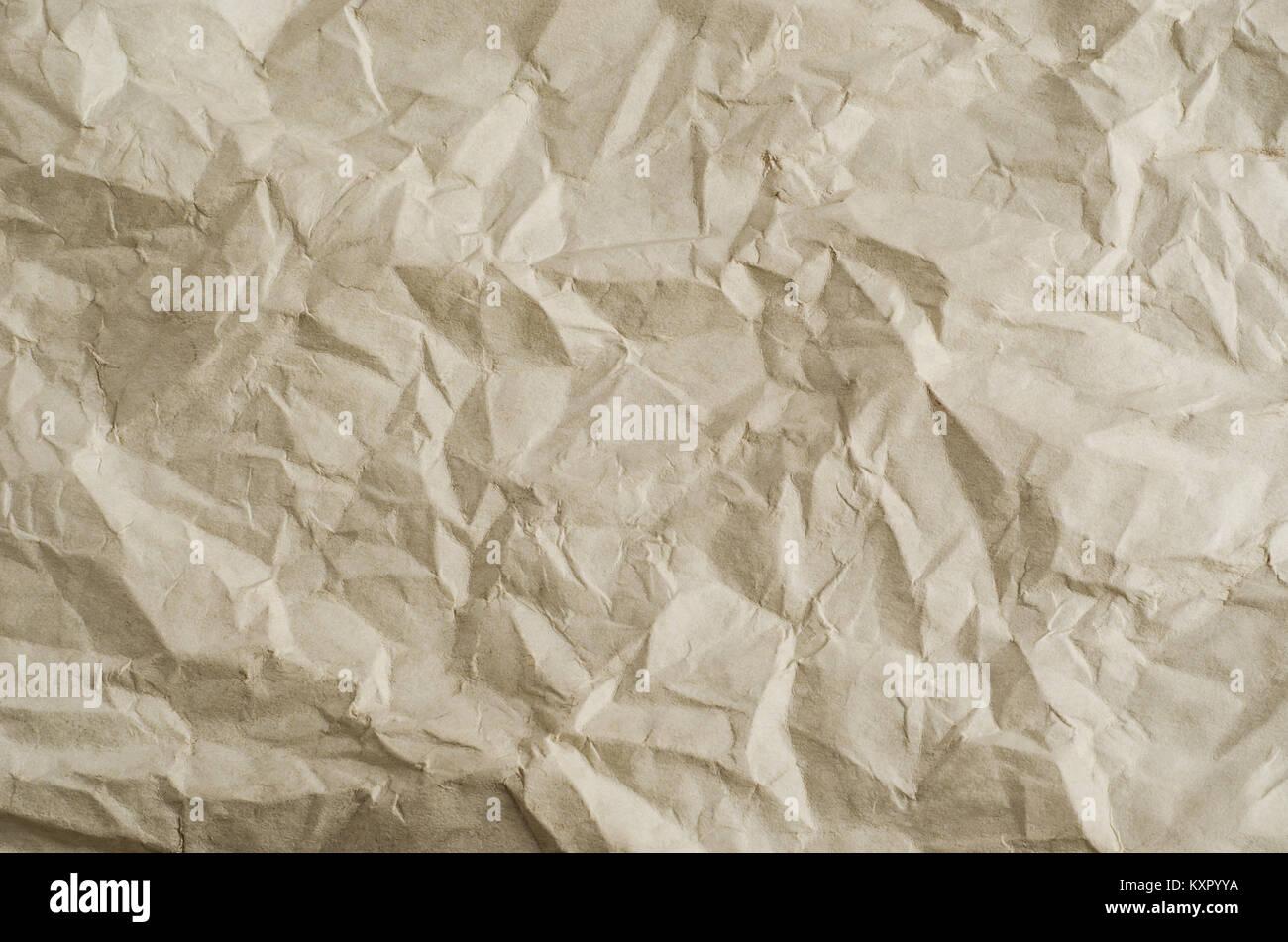 Papier froissé, plié et déplié paper texture de fond dans une teinte parchemin neutre. Photo Stock