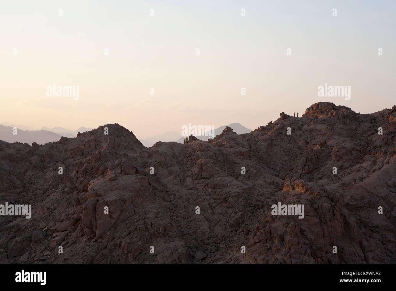 Deux personnes dans la distance debout au sommet d'une montagne dans la lumière du soir ayant une photo prise. Banque D'Images