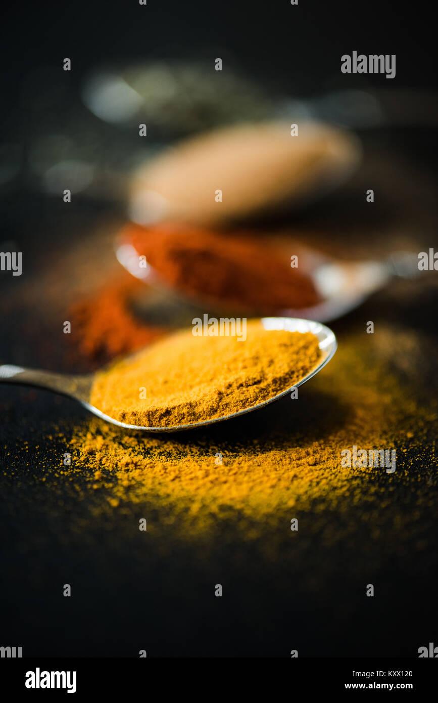 Close up de différentes épices et herbes dispersées dans cuillère en métal Photo Stock