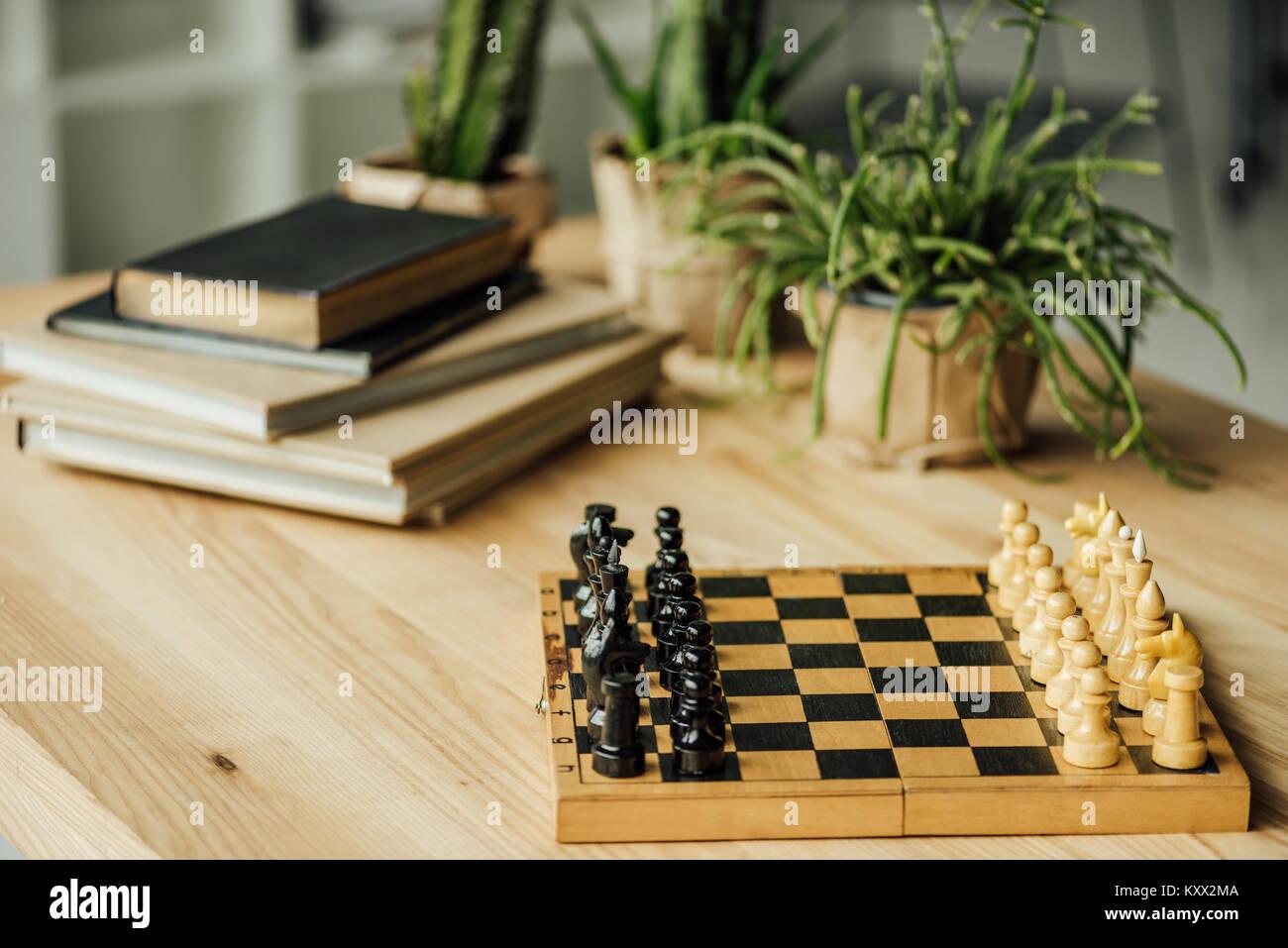 Conseil d'échecs défini pour un nouveau jeu sur la table avec des livres et des plantes en pots Banque D'Images