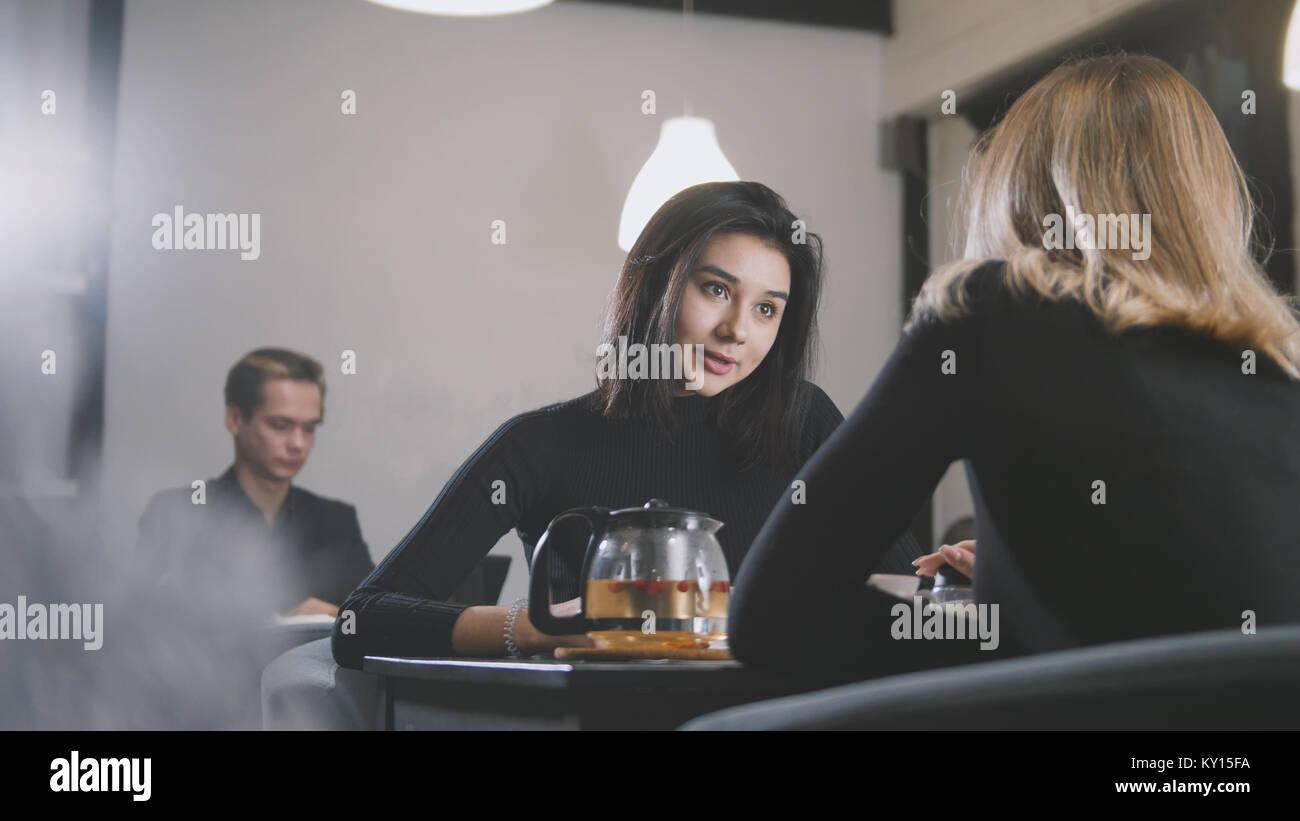 Jolie jeune femme aux cheveux noirs de parler avec ma copine dans le café Photo Stock