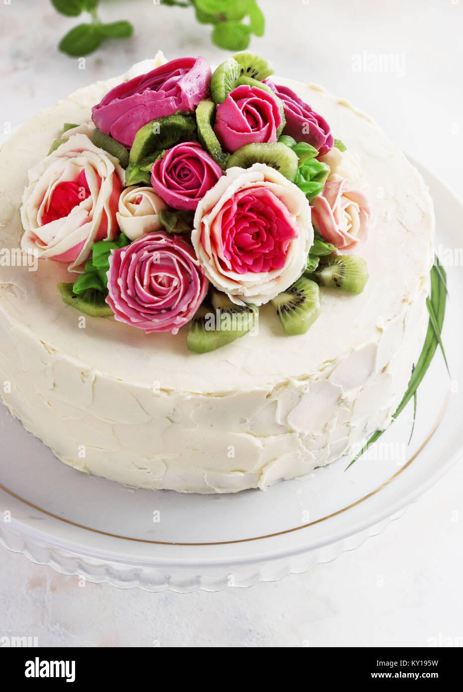 Gâteau d'anniversaire avec des fleurs rose sur fond blanc Photo Stock