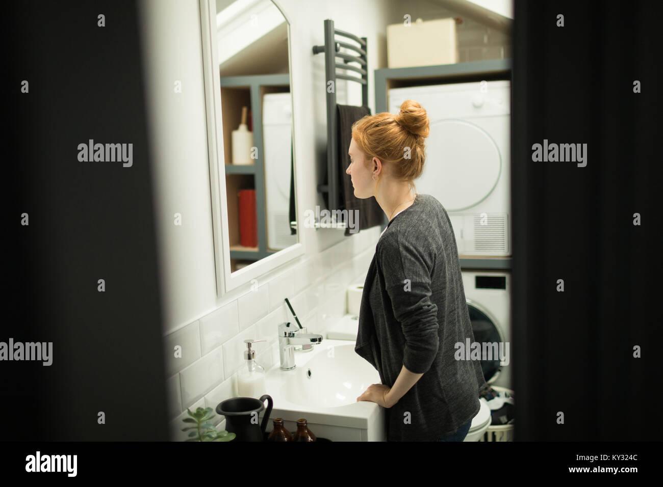 Jeune femme à la recherche de miroir de salle de bains Photo Stock