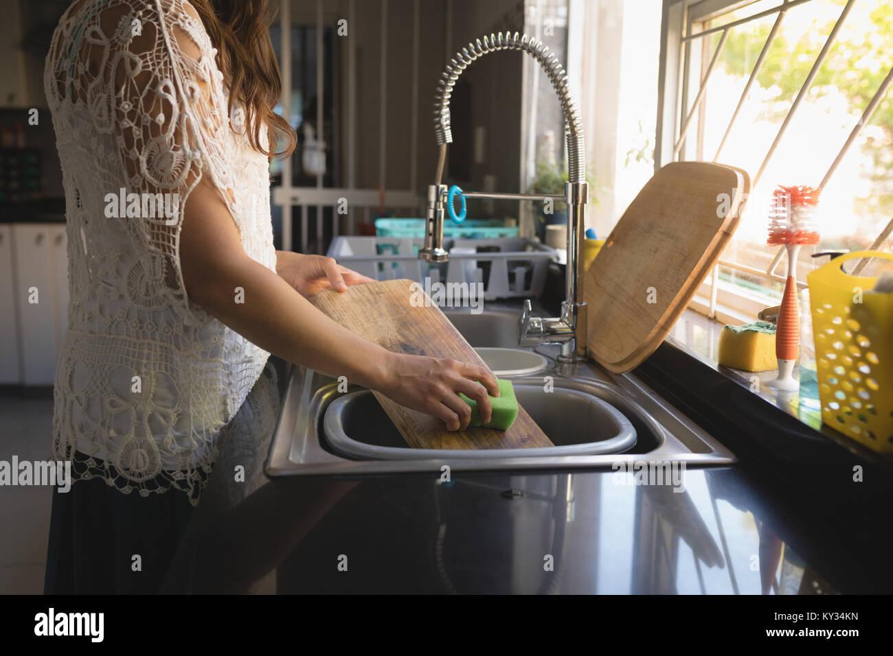 Planche à découper femme lave dans le lavabo Photo Stock