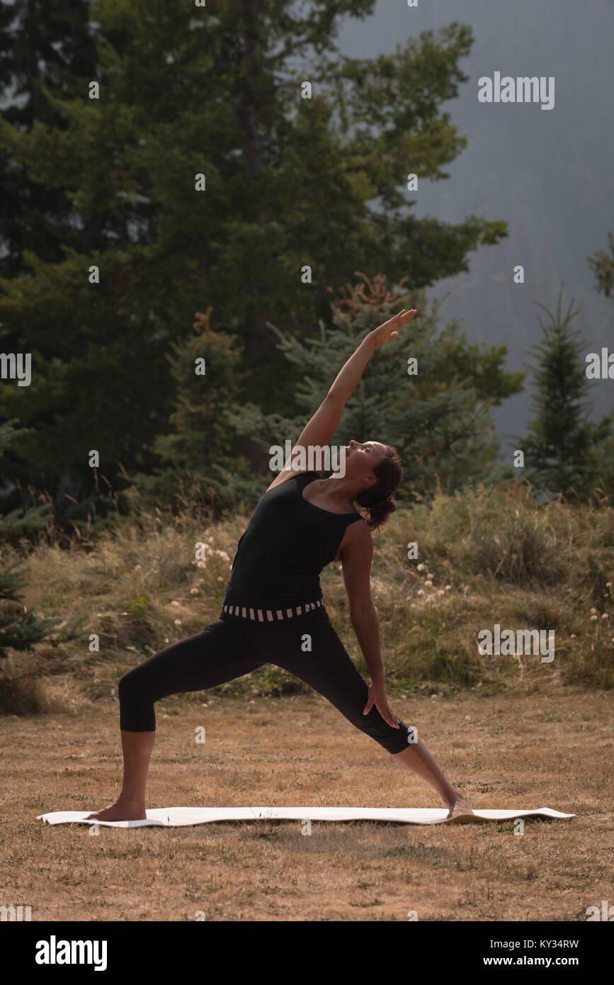 Fit woman performing exercice s'étendant sur un terrain ouvert Photo Stock