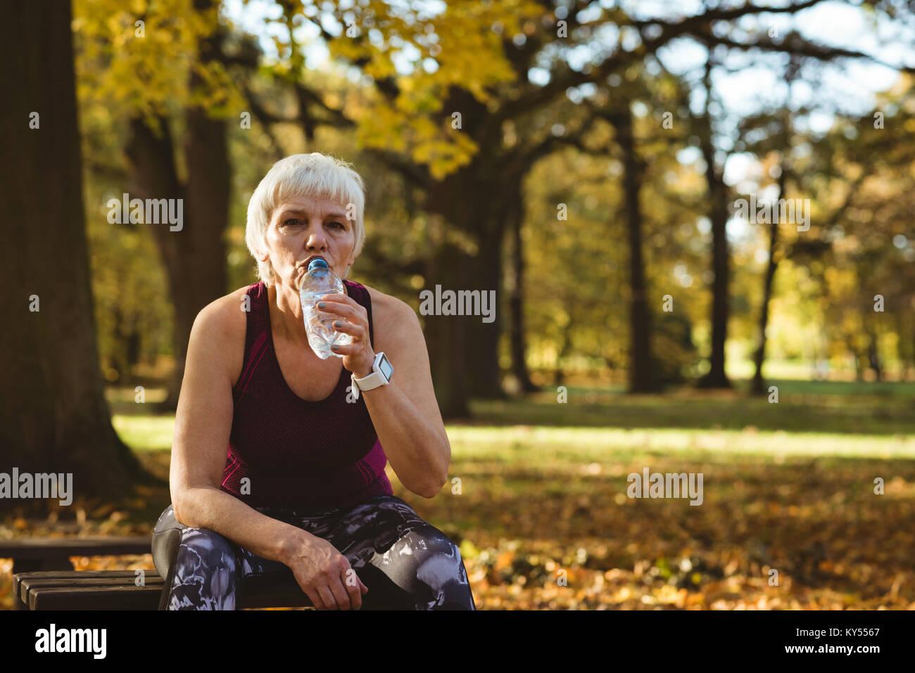 Senior woman l'eau potable dans le parc Photo Stock