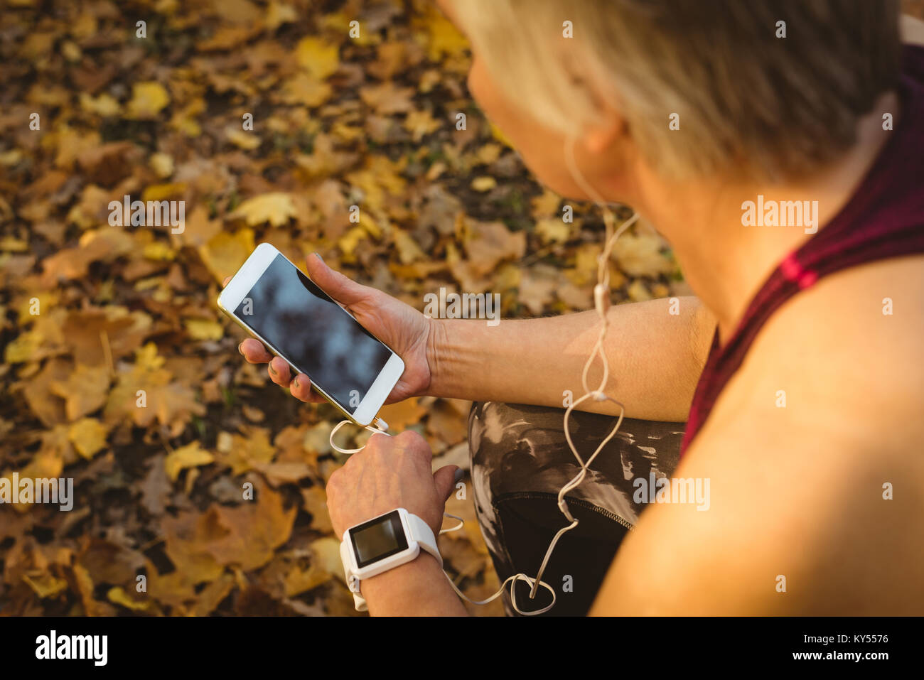 Senior woman listening to music in the park Photo Stock