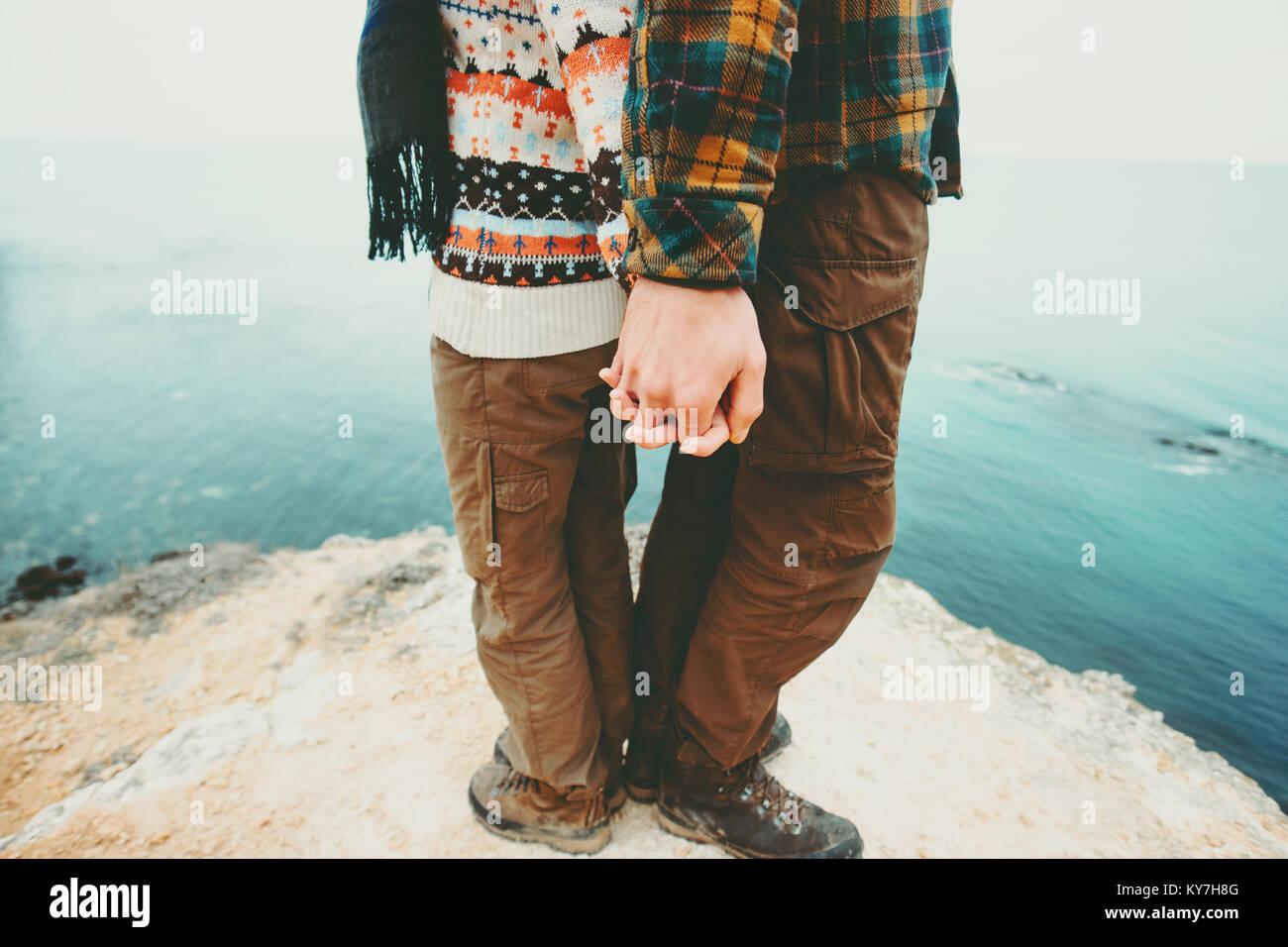 Couple Homme et Femme tenant la main debout sur falaise au-dessus de paysage de mer et l'amour avec une assurance Photo Stock