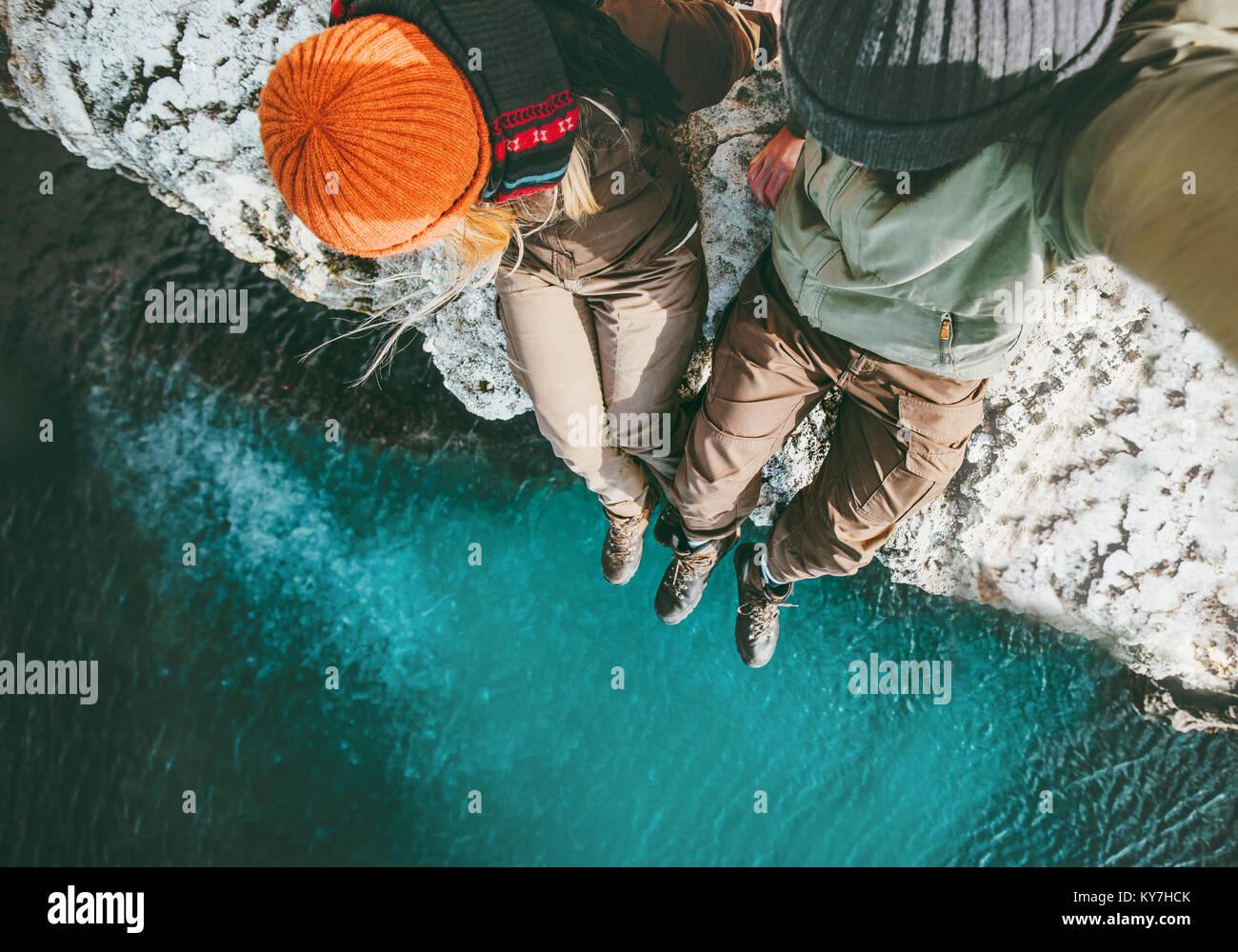Couple in love l'homme et la femme assis ensemble au-dessus de la mer sur la falaise avec une assurance vie Photo Stock