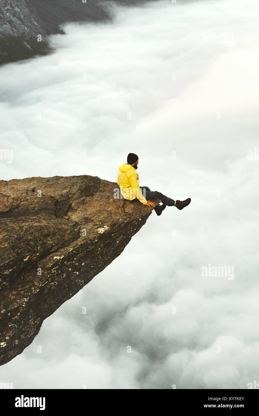 Voyageur rencontrez l'aube de l'homme assis sur le bord de la falaise rocheuse Trolltunga en Norvège Photo Stock