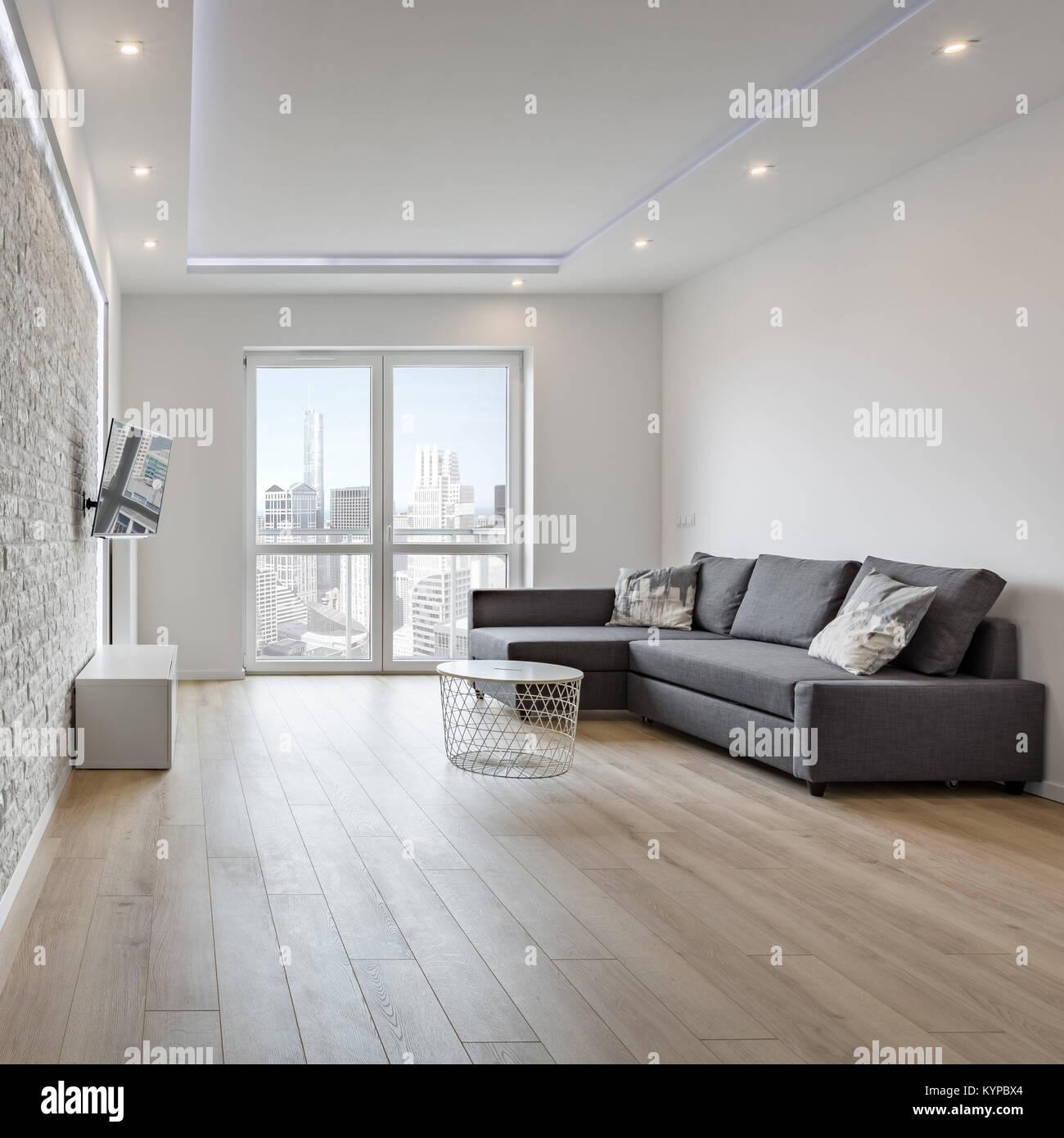 White Salon Avec Canape Gris Et Mur De Brique Banque D