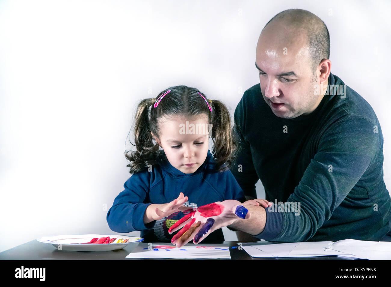 Jolie petite filles est sa peinture peintures colorées à la main les pères Banque D'Images
