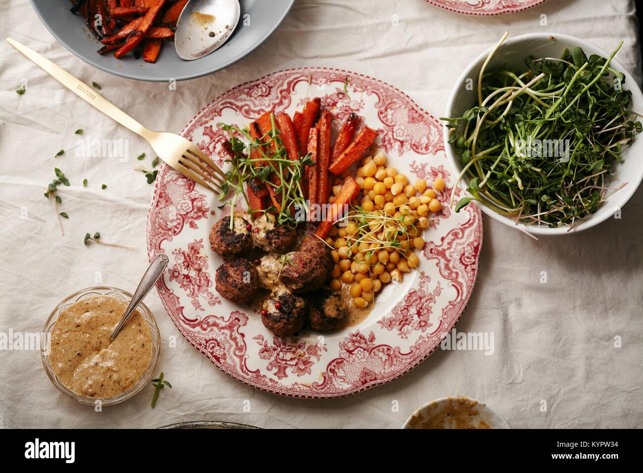 Swedish meatballs garni de sauce béchamel et micro-verts avec les pois chiches et les carottes caramélisées servi sur plaque porcelaine vintage sur l'onglet linge Banque D'Images