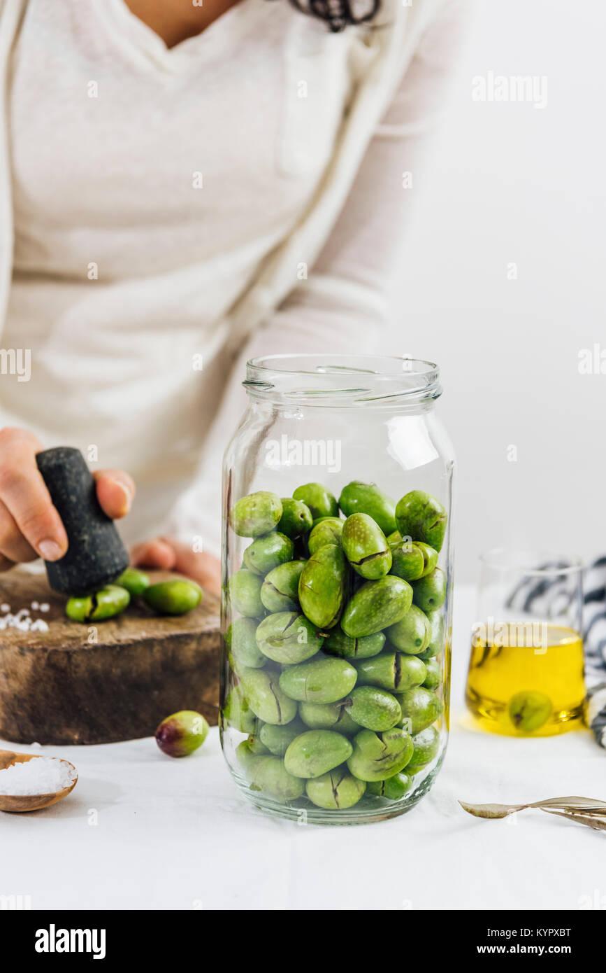 Une femme la fissuration des olives pour le saumurage. Un bocal de verre rempli d'olives vertes, une tasse en Photo Stock