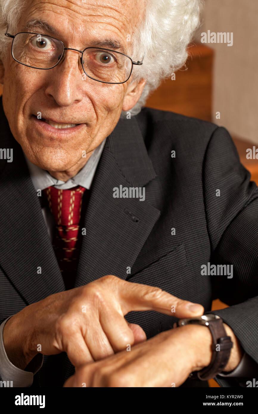 Impatients, vieil homme en montrant sa montre. Looking at camera avec un regard d'exaspération sur son Photo Stock