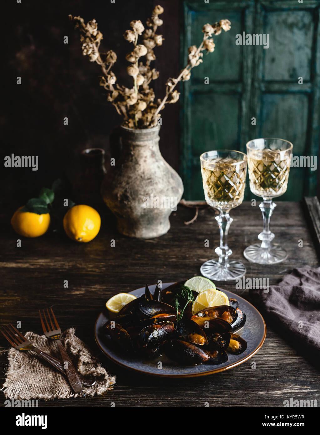 Moules cuites avec des coquillages servis sur plaque avec deux verres de vin blanc sur la table en bois Photo Stock