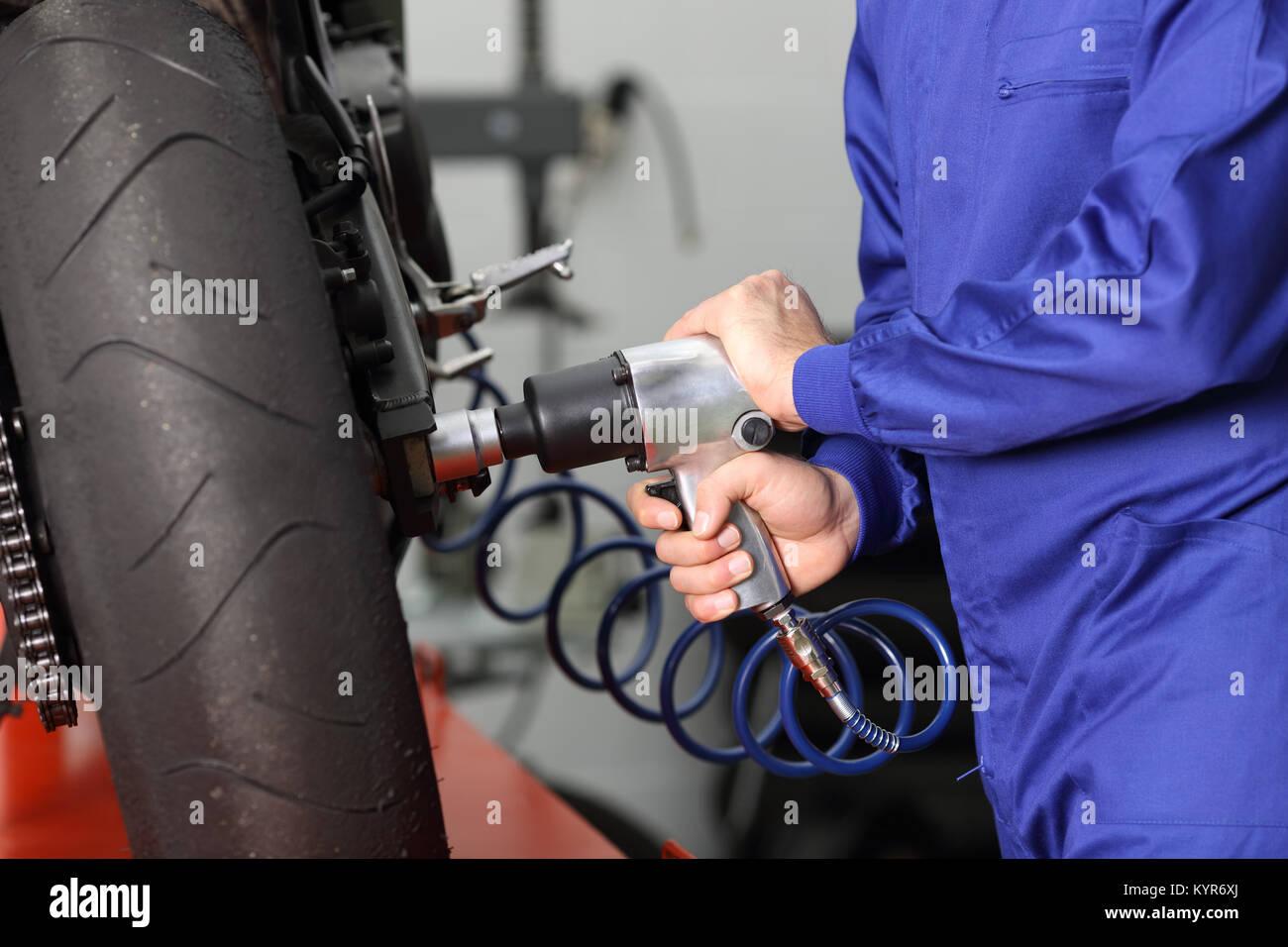 Gros plan d'une main usinb mécanicien de motocyclettes de travail un pistolet pneumatique pour serrer un Photo Stock
