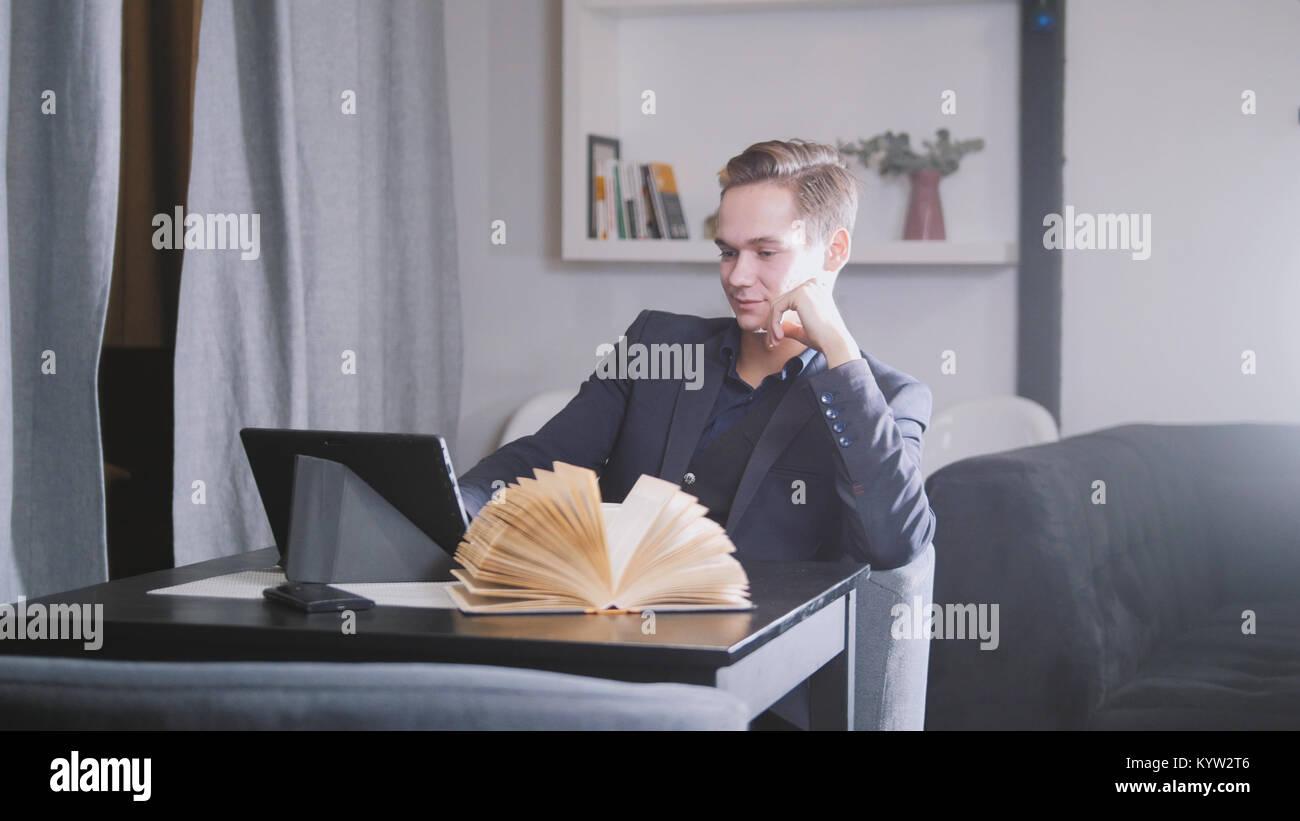 Jeune homme assis avec ordinateur portable et réserve en café avec café Photo Stock
