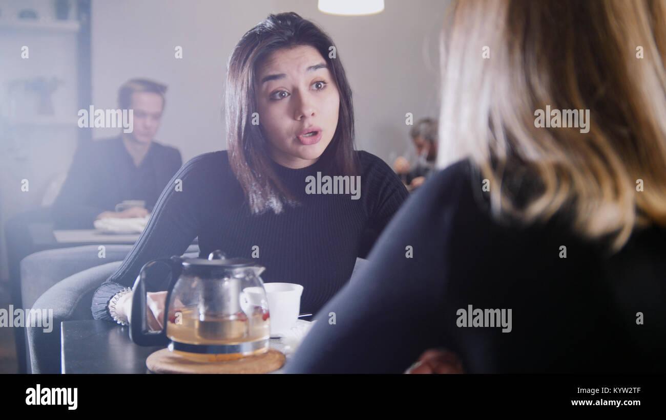 Jeune femme aux cheveux noirs avec des cheveux noirs de boire du café et parler avec ma copine dans le café Photo Stock