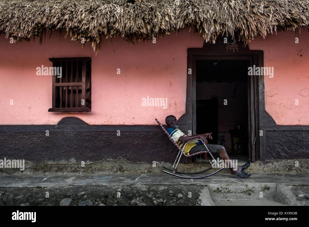 Un vieil homme est assis colombien dans un rocking-chair en face de sa maison à San Basilio de Palenque, un village de la région des Caraïbes de la Colombie. Banque D'Images